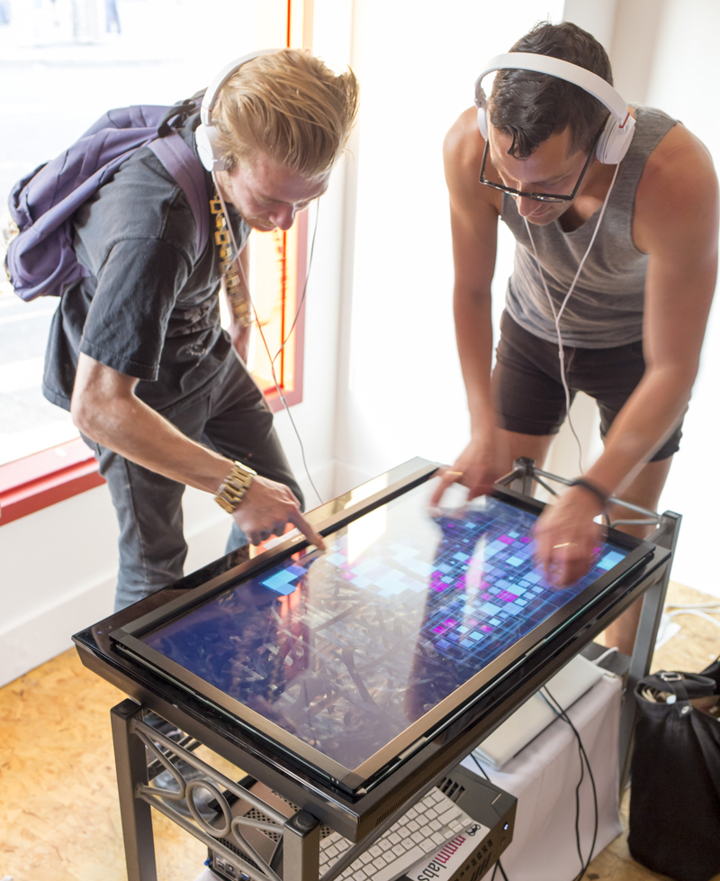 two guys using a touchscreen to interact with the artwork Beckon